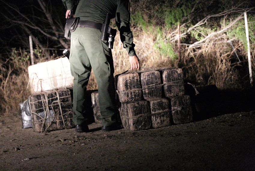 After chasing away the smugglers using rafts to bring drugs across the river, Border Patrol and Texas DPS agents inspect several large packages of marijuana abandoned near the Rio Grande shoreline near Roma, Texas, on March 8, 2016. The packages were later found to weigh 313 pounds, making them worth an estimated $240,000.