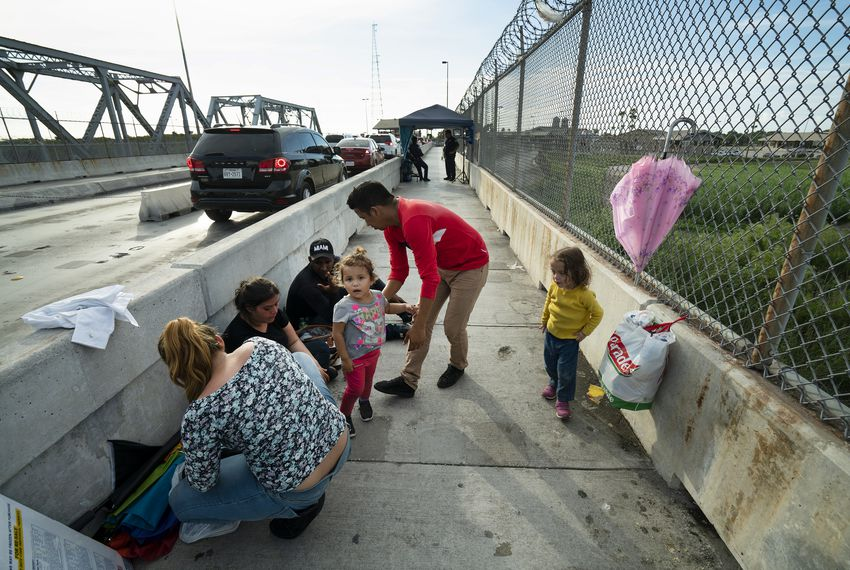 Families from Guatemala and Honduras wait for their opportunity to apply for asylum at an international bridge at the U.S.-Mexico border.
