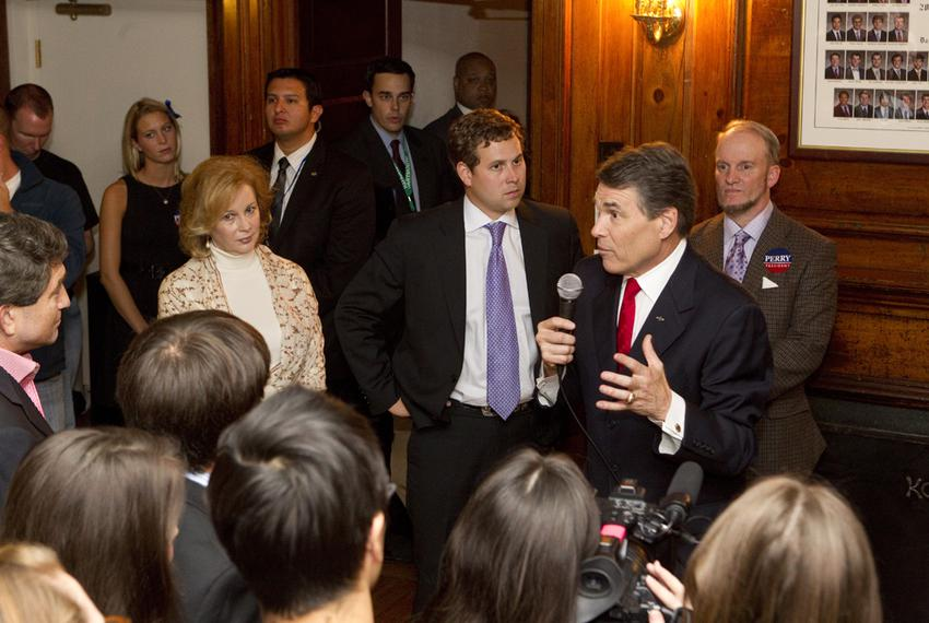 Rick Perry, r, speaks at a Dartmouth fraternity house as wife Anita Perry, r, and son Griffin, c, listen following the Dartm…