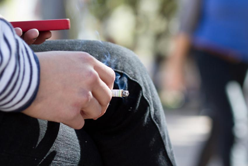 English student Kristin Miller smokes a cigarette and checks her phone on the South Mall between classes.