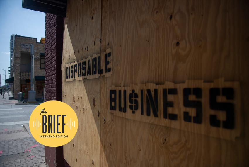 """A business on the corner of Brazos Street and East 5th Street is boarded up with """"Disposable Business"""" written on the boards…"""