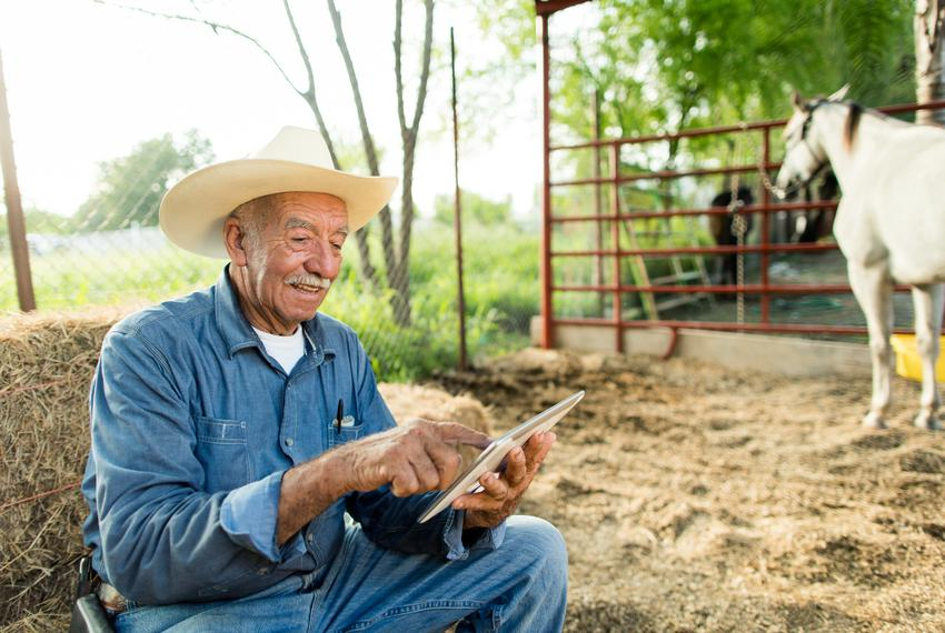A cheerful senior man sitting on haystack at a horse ranch, using a digital tablet and smiling.
