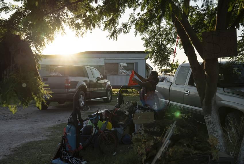 Liliana Ruiz, arranges used items in a garage sale that she is having outside of her house in a colonia in Edinburg.  Ruiz...