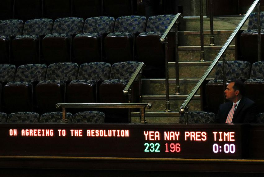 The gallery above the floor of the U.S. House of Representatives display board shows the final vote tallies on a resolution …