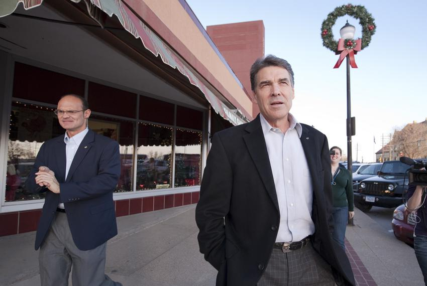 Gov. Rick Perry walking down Adams Street in Creston, Iowa, with Department of Public Safety trooper Chris Brannen after s...