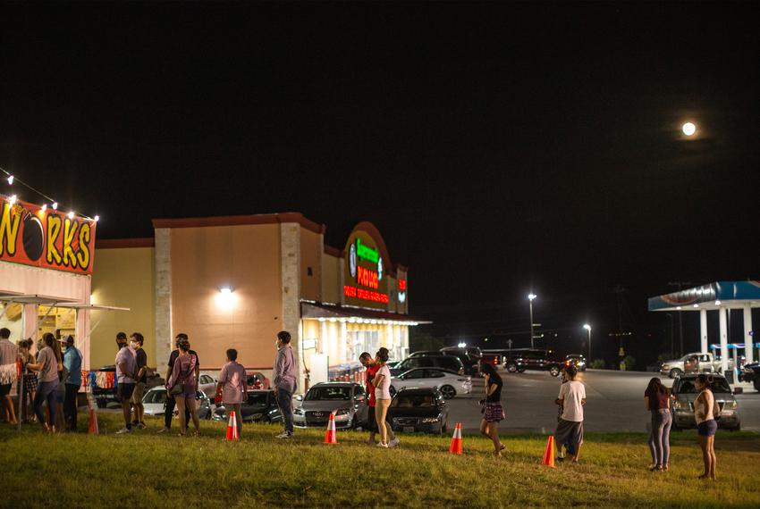 People stand in a socially-distanced line to buy fireworks at a fireworks stand in Buda on the Fourth of July.