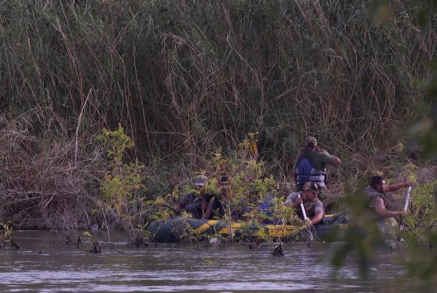A raft loaded with undocumented immigrants navigates the Mexican side of the Rio Grande across from Ruperto Escobar's ranch …