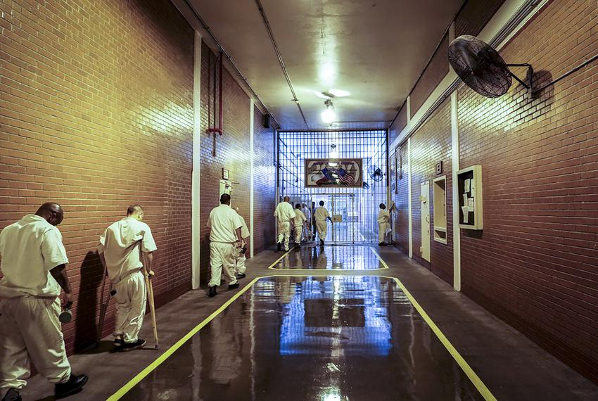 Inmates shuffle down a hallway at Brazoria County's Darrington prison in July 2017.