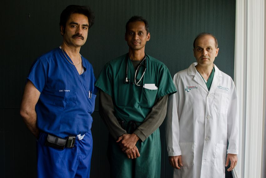 Doctors Harish Chandna, Ajay Gaalla, Dakshesh Parikh stand for a portrait in their offices' waiting room.