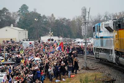 People pay their respects Thursday as the train carrying the casket of former President George H.W. Bush passes by along the route from Spring to College Station.