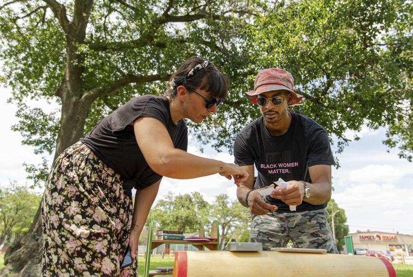 Helena Acosta and Josef Pierre engage in an activity as part of Violette Bule's public art installation 'Rethinking Your Nei…