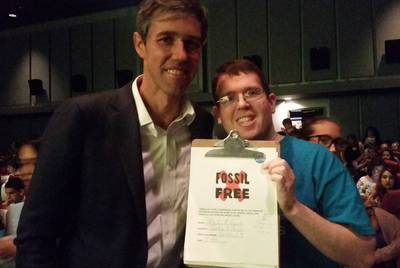 Mickey Fetonte, a member of the environmental group 350 Austin, shows the pledge Beto O'Rourke signed that he would not take campaign donations from the oil, gas and coal industries.