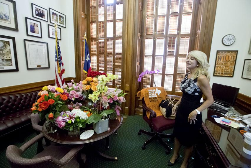 State Sen. Wendy Davis, D-Fort Worth, in her office on June 27, 2013, with flowers from supporters after her filibuster of a…