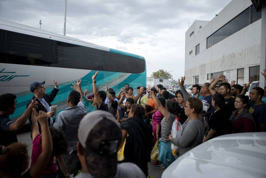 A group of migrants raise their hands after Texas Tribune reporter Jay Root asked how many planned on returning to Central...