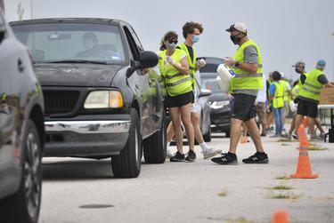 Volunteers load boxes of food into a car during a drive-thru food distribution hosted by the Central Texas Food Bank at the Travis County Expo Center on June 30, 2020 in Austin.