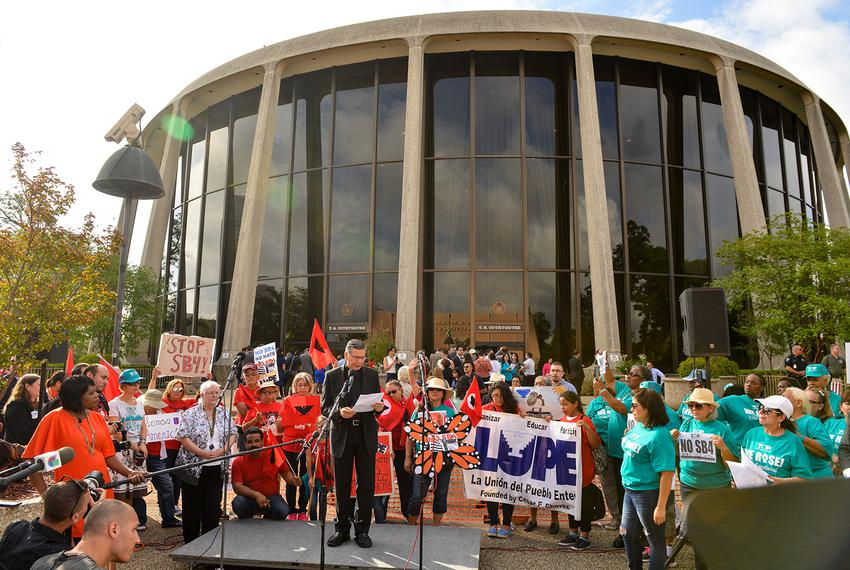 San Antonio Archbishop Gustavo Garcia-Siller speaks to protesters in front of the federal courthouse where U.S. District J...