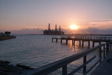 The sun sets on a fishing pier, damaged by Hurricane Harvey in 2017, in Port Aransas, Texas, on June 6, 2018. Three offshore oil rigs stand at attention in the distance.