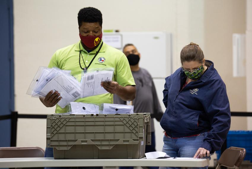 Harris County election workers process the MBB data cards which contain ballot results at the NRG Arena in Houston on Tuesda…