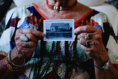 Mina Verton holds up a photo of her family's farmhouse, which was swept away in the 1953 North Sea flood.