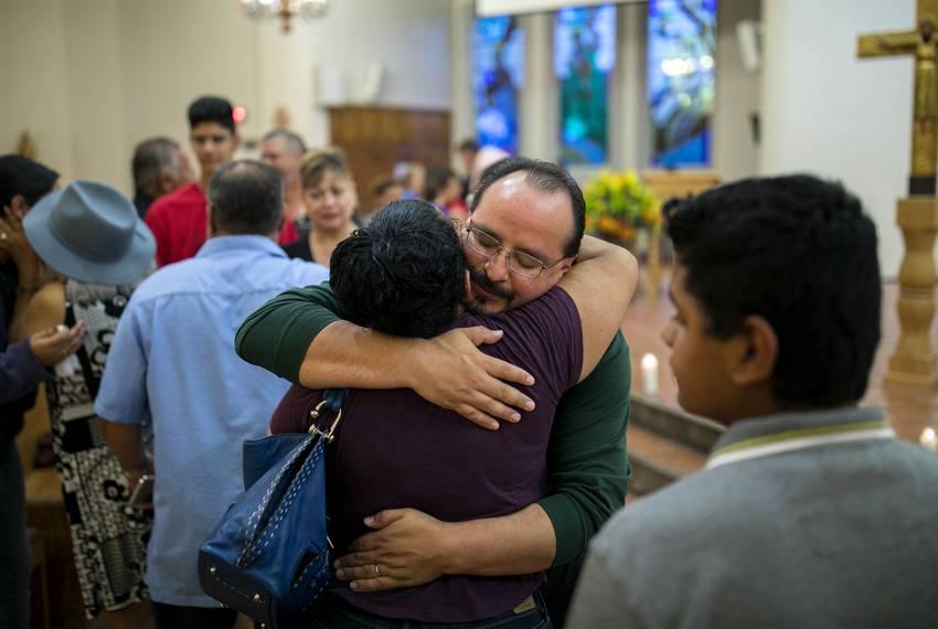 A man and woman embrace as Nadra Alvarez and her mother Angelina Alvarez pray after a candlelight vigil at a Catholic chur...