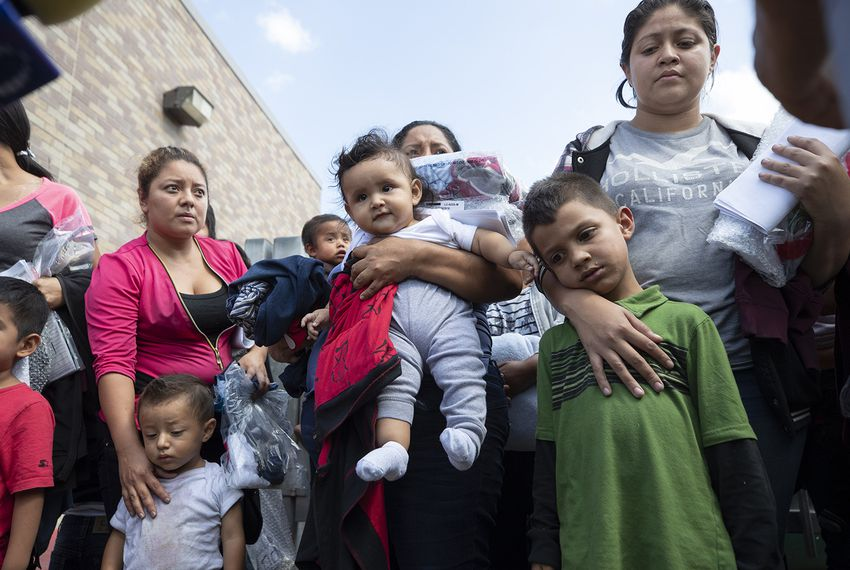 About 25 immigrant mothers and their children caught coming across the Texas-Mexico border are released at the McAllen bus station wearing ankle monitors, on June 22, 2018.
