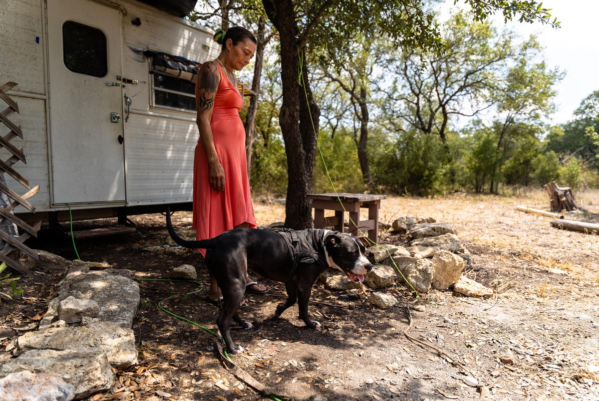 Susan and her daughters dog moose in front of the trailer they are staying in on her cousins land in Killeen.