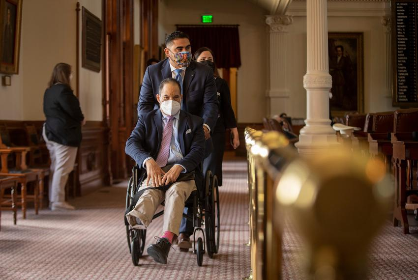 Houston state Rep. Armando Lucio Walle pushes Rep. Garnet Coleman in a wheelchair on the House floor on Aug. 19, 2021. State…