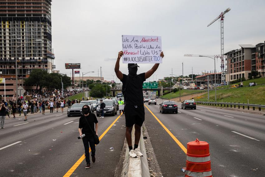 Demonstrators block traffic and march past vehicles on I-35 during a protest against police violence in Austin on May 31, 20…