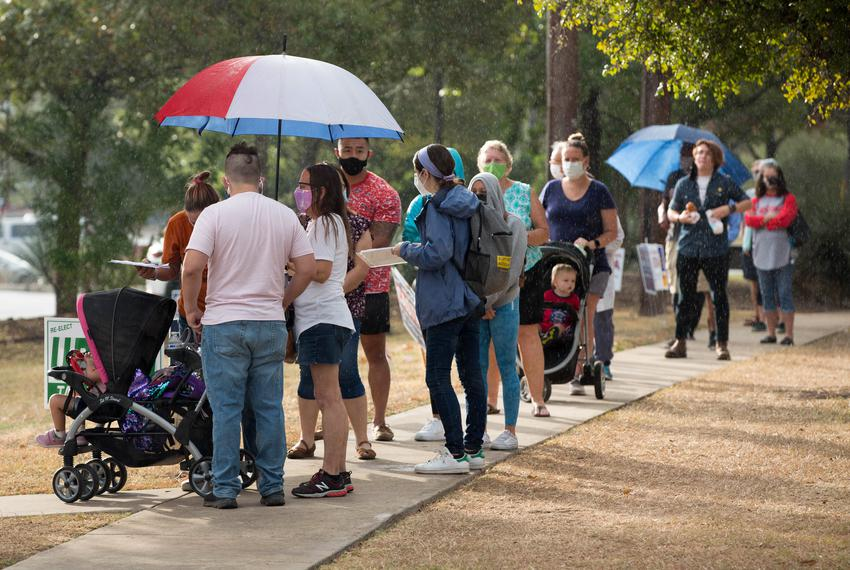 Bexar County residents stand in the early morning rain outside the Julia Yates Semmes Library on Oct. 20, 2020. The library …