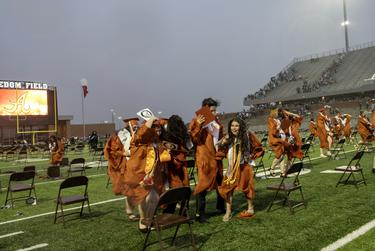 Graduates rush off the field as a storm hits during the ceremony in Iowa Colony. Viky Cruz, 18, whose house burned down during the school year, graduated from Alvin High School on Sat, June 6, 2020. (May-Ying Lam for the Texas Tribune)
