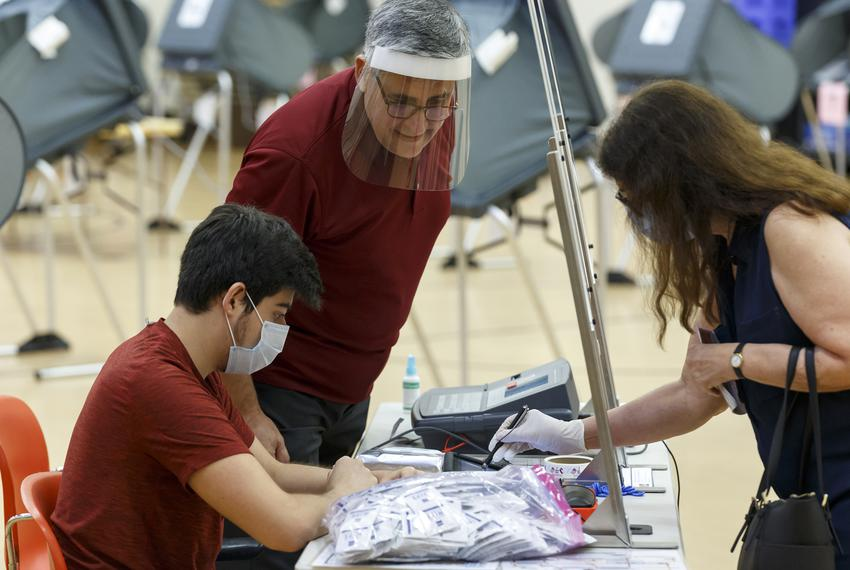 Voters check in with poll workers behind glass barriers at the Metropolitan Multiservices Center for the delayed primary r...