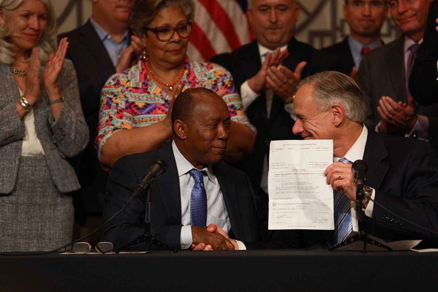 Gov. Greg Abbott presents Houston Mayor Sylvester Turner with a $50 million check for Hurricane Harvey relief during a news conference in Houston on Friday, Sept. 29, 2017.