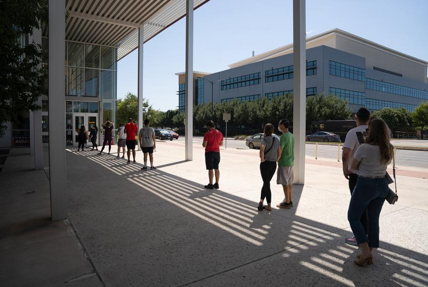 People wait to vote in triple digit heat at the AISD Performing Arts Center in Mueller on July 14, 2020.