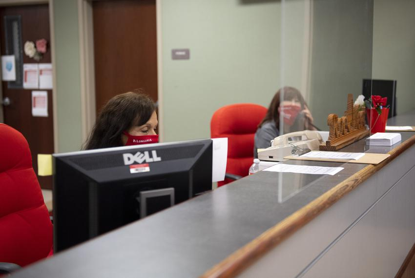 Receptionists work behind a plexiglass barrier in the front office, one of the only areas with plexiglass installed, at Juds…