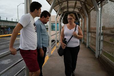 Immigration attorney Jodi Goodwin talks to Bernardo and Grisber Calero on the Mexican side of the international bridge in Reynosa on Sept. 15, 2018.
