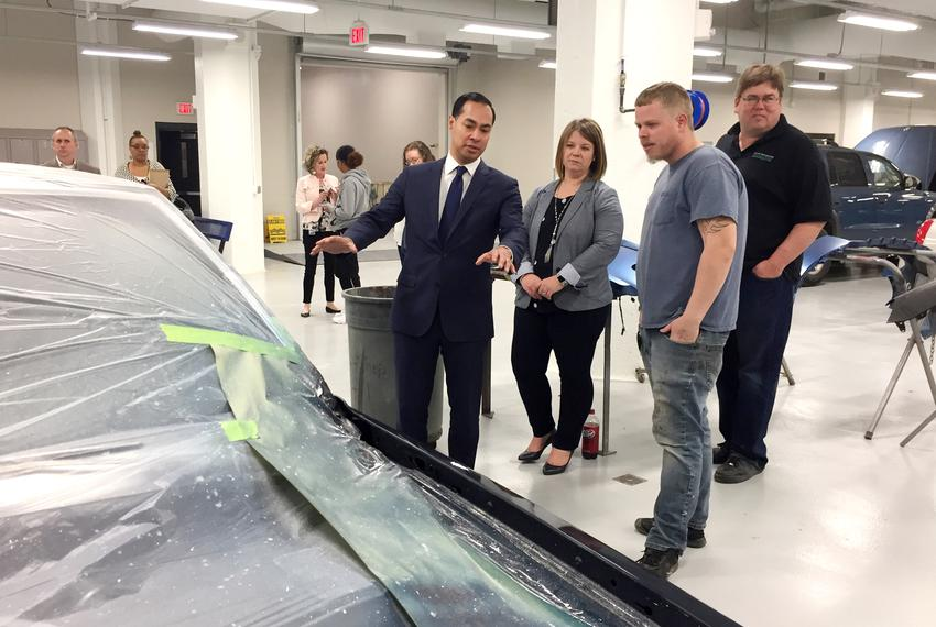 Former U.S. Housing and Urban Development Sec. Julian Castro tours the auto-painting shop of Central Campus, a technical h...