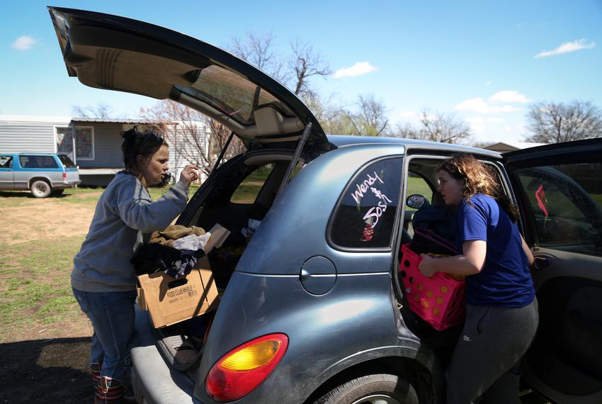 Wendy Bryant and her daughter, Amanda Garrison, unpack the family car in Del Leon, on March 25, 2021.