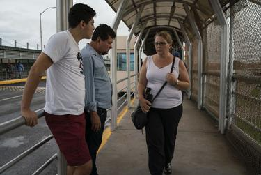 Immigration attorney Jodie Goodwin talks to Bernardo and Grisber Calero on the Mexican side of the international bridge in Reynosa, Tamaulipas on Sept. 15, 2018.