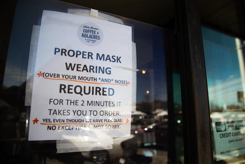 A sign outside of Little Brother Coffee & Kolaches asks customers to wear a mask inside the South Austin business on March 3…