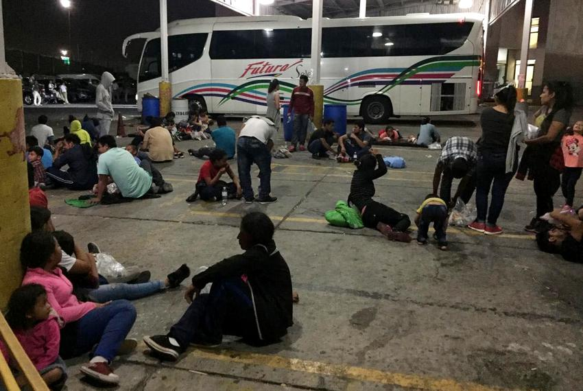 Chartered buses are parked behind a group of migrants at an immigration checkpoint in Nuevo Laredo. The buses are scheduled …