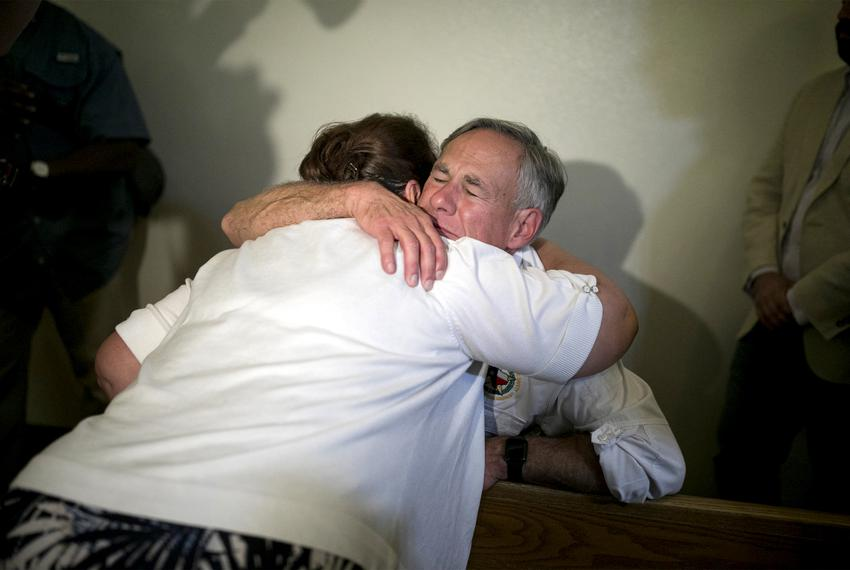 Texas GOP Gov. Greg Abbott embraces a woman after a candlelight vigil at a Catholic church, Saturday, August 3, 2019, in E...