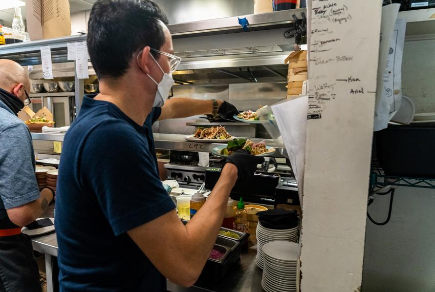 Owner Eric Silverstein takes food from the Bar Peached kitchen to one of his customers on Aug. 13, 2020.