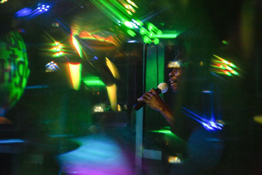Earl Houston, an employee of G Willickers Pub in Arlington for 21 years, sings karaoke into a microphone with a single use p…