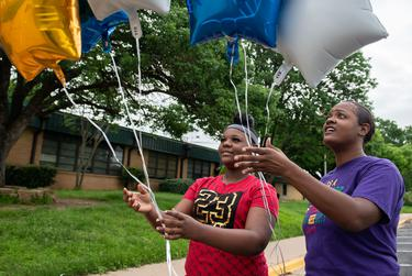 G.W. Carver Middle School seventh grade student Tabitha Hawkins, 13, left, and mother Tobie release balloons in front of a memorial outside of the school for Principal Phillip Perry, 49, who died from coronavirus on March 31.