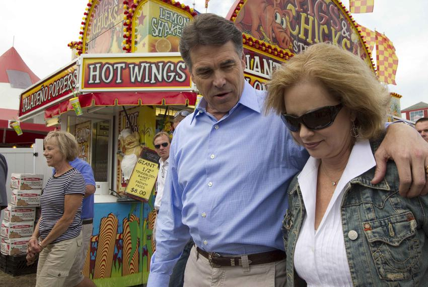 Texas Governor and presidential hopeful Rick Perry walks through the Iowa State Fair with wife Anita Perry (r) on Monday, tw…