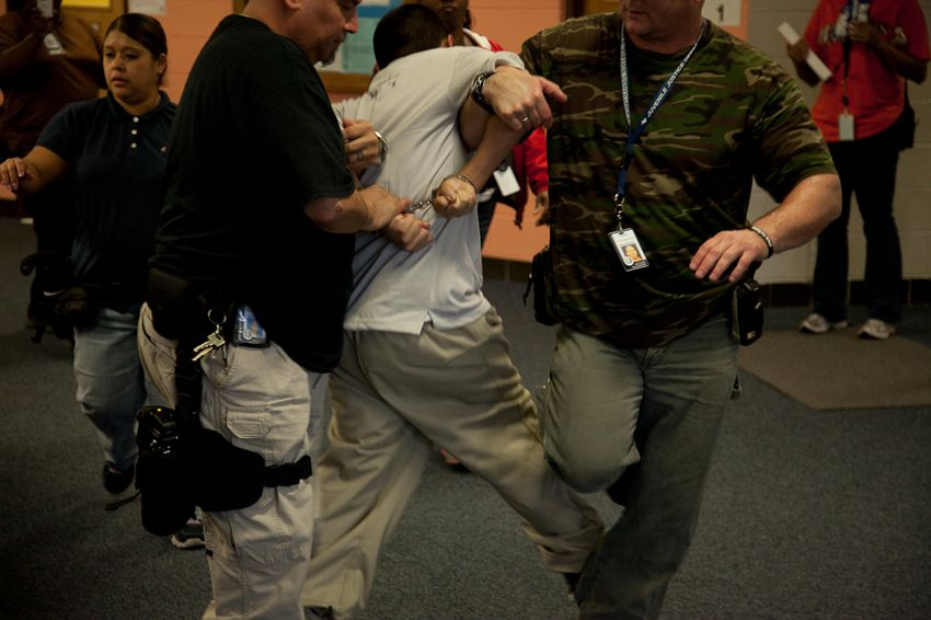 A detainee is removed from the school building after an outburst during class.