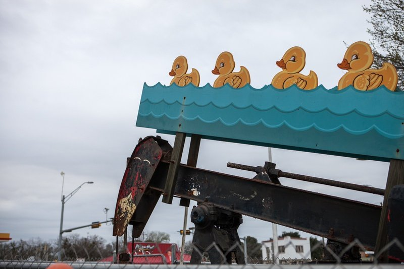 In a grocery store parking lot, these swimming ducks bob up and down with the pump jack.