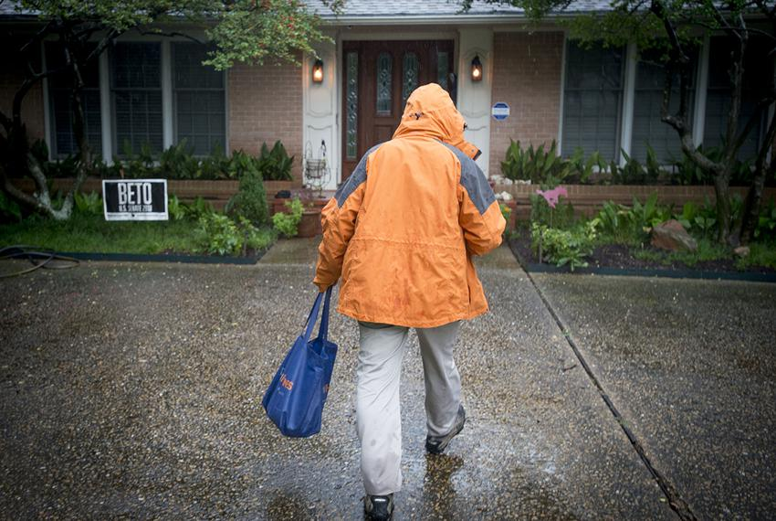 State Sen. Don Huffines walks through the rain to knock on a door where a Beto O'Rourke supporter lives, in Dallas on Oct. 1…