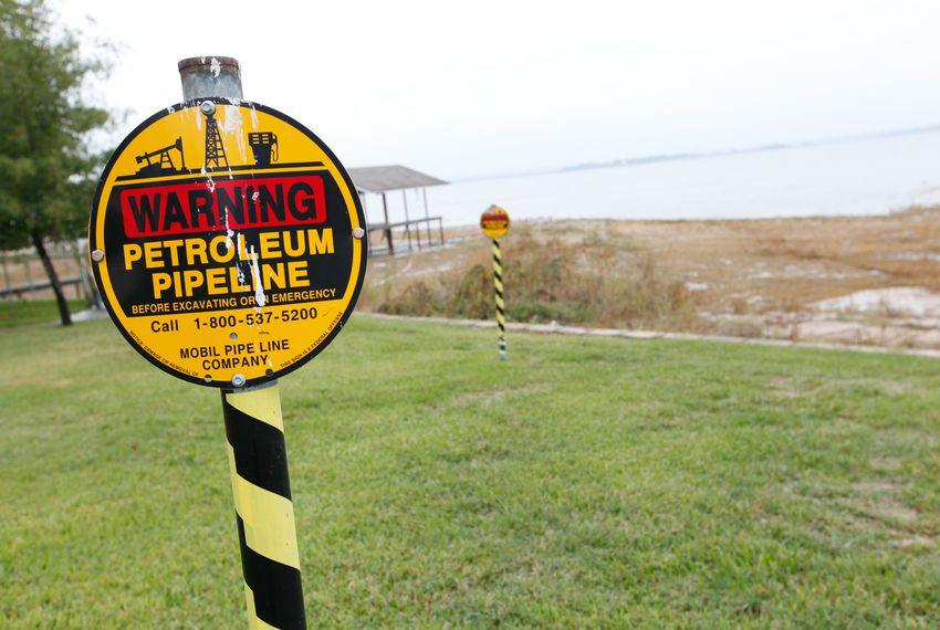 A warning sign indicates where the Exxon Mobile Pegasus pipeline cuts through the Harbor Point Estates neighborhood and into the Cedar Creek Reservoir in Gun Barrel City.