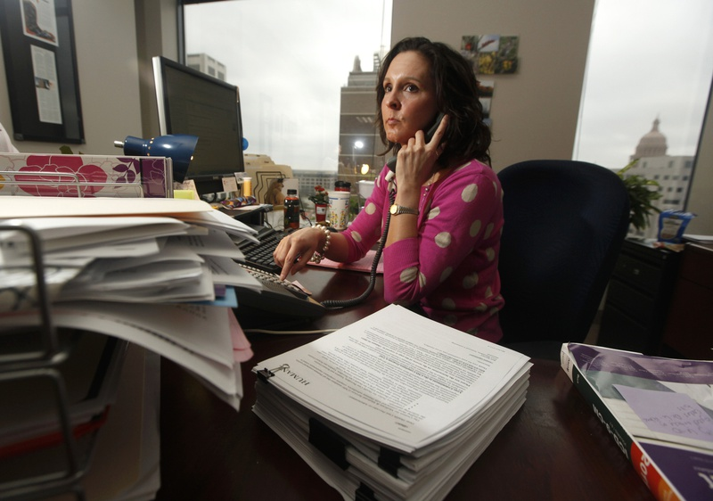 Genevieve Davis, director of payment advocacy for the Texas Medical Association working the computer and her phone at her desk in Austin, Texas February 20, 2012.